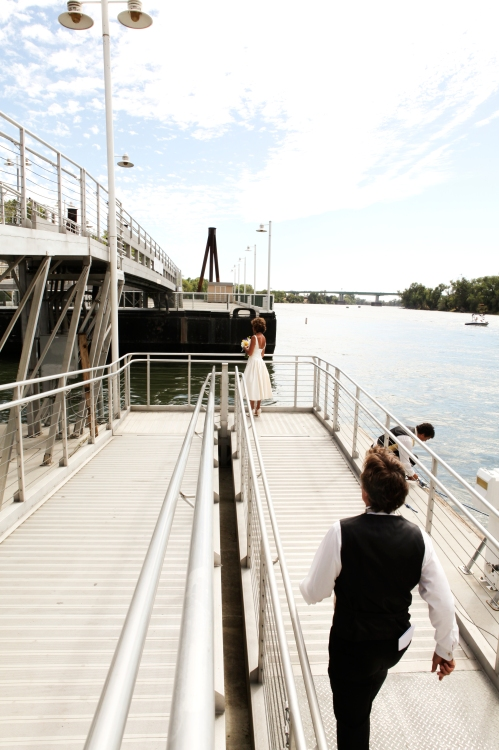 Bride and groom on river dock
